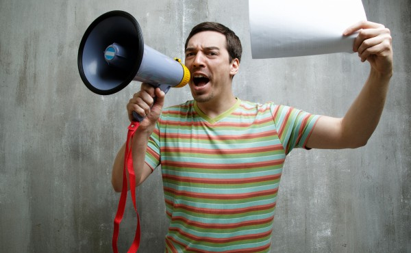man shouting into a megaphone and holding a white sheet of paper on a background of gray textured wall