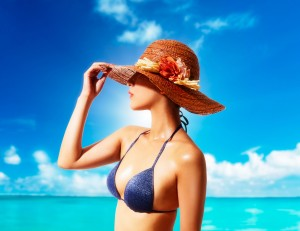 Woman with a straw hat and bikini on the beach. Summer vacation fashion style image.