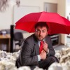 Scared businessman with umbrella protecting from papers in the office