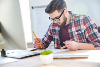 Handsome concentrated man working with blueprint using ruler and pencil
