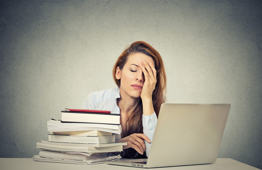 tired sleepy woman sitting at her desk with books computer