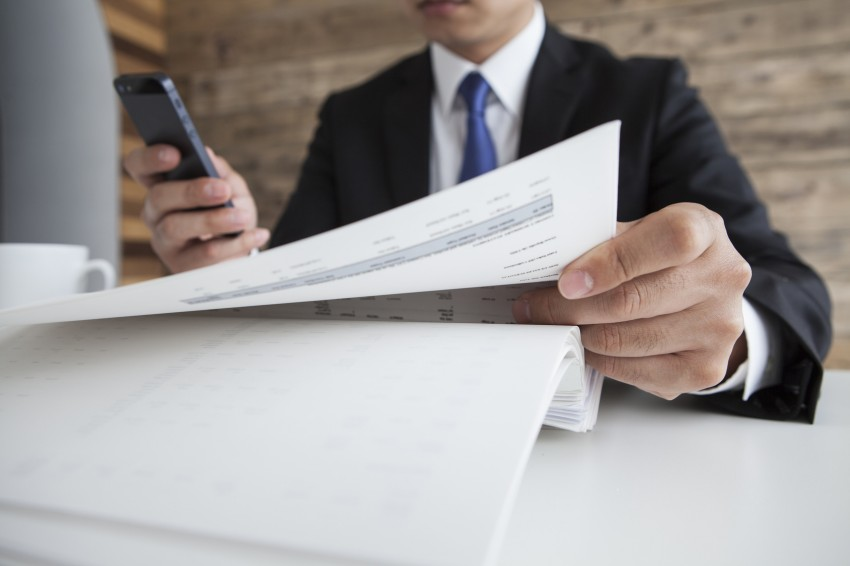 Businessman looking at the article with a smartphone