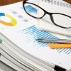 Document management. Paperwork. Business concept.Pile of documents on wood background. Graph, glasses, note and pen.
