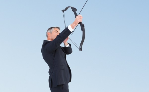 Composite image of businessman shooting bow and arrow